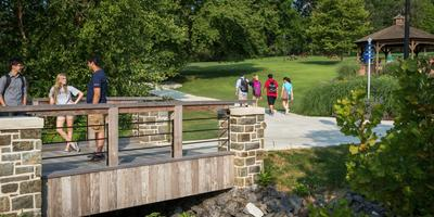 Penn State Brandywine students walk across a bridge on campus.