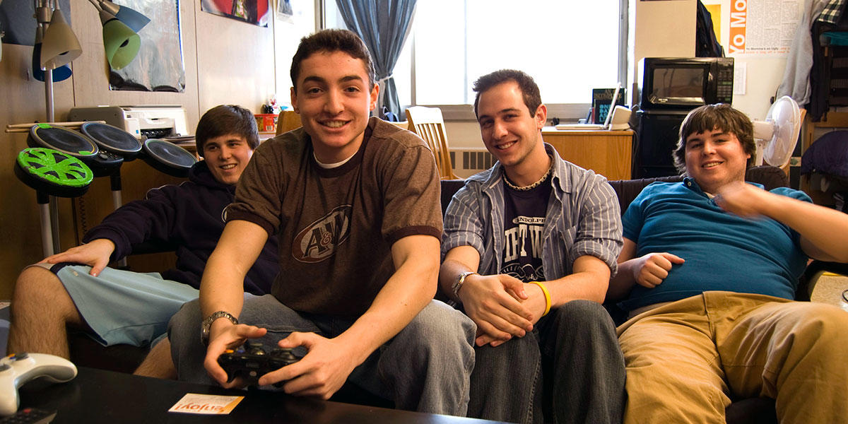 four smiling students playing video games