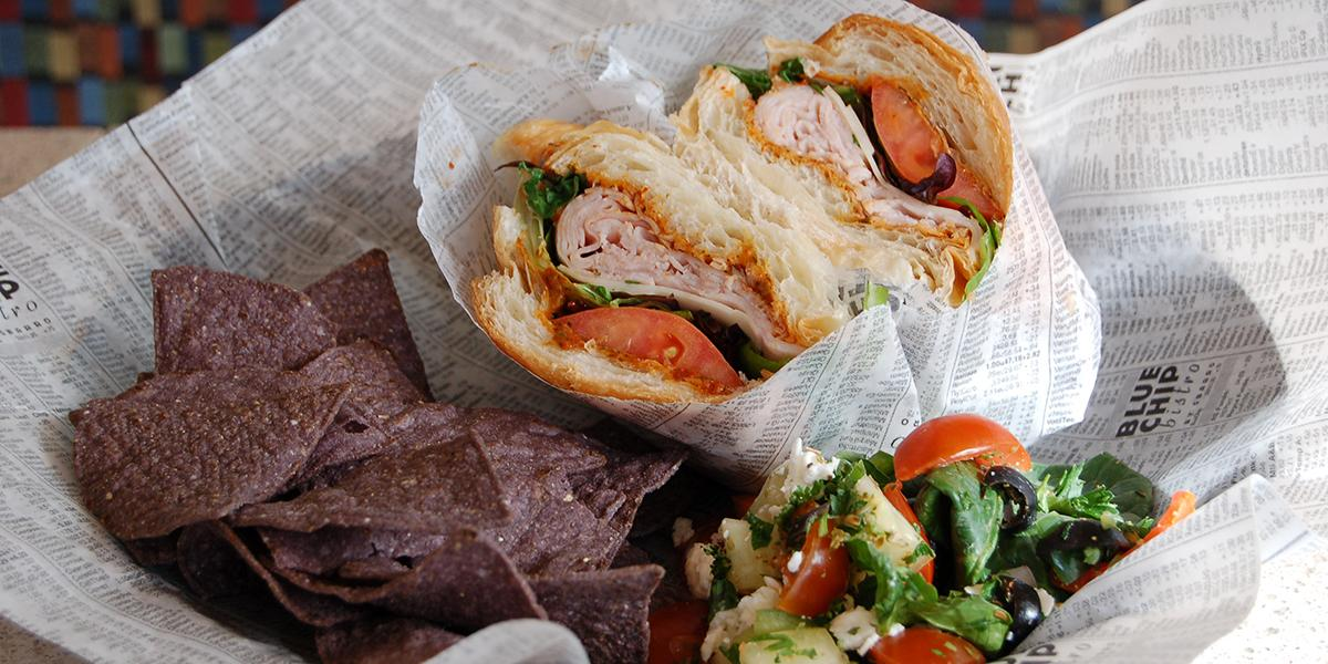 A close-up of a turkey sandwich with a side of tortilla chips and pasta salad.
