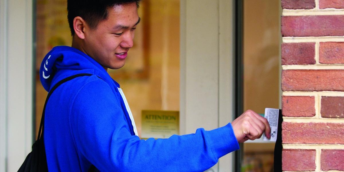 A Penn State student swipes his id card to enter his residence hall