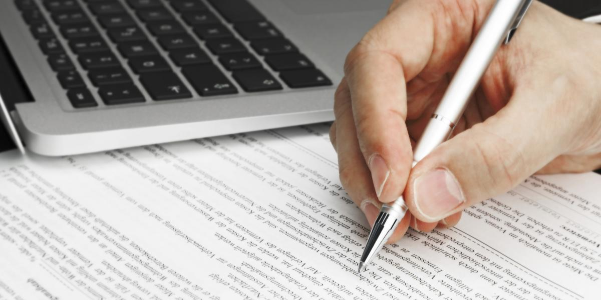 hand holding pen above paper