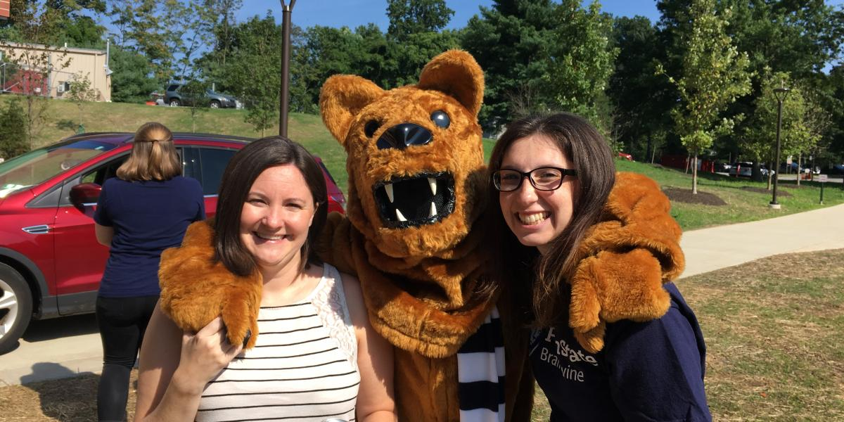 Nittany Lion mascot posing with students at fall arrival
